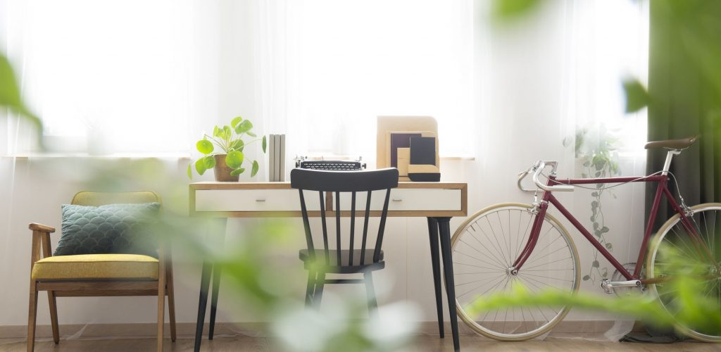 Wooden desk standing by large, bright windows next to an old, vintage red bike in freelancer's room interior